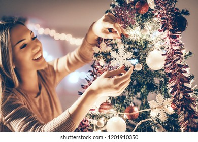 Beautiful smiling young woman decorating christmas tree with Christmas ornament at home.