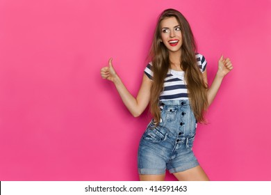 Beautiful smiling young woman in dungarees and blue striped shirt showing thumbs up and looking away. Three quarter length studio shot on pink background.