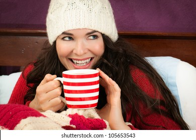 A beautiful smiling young woman enjoying a hot drink under the blankets in bed.