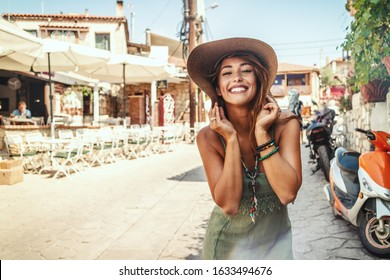 A beautiful smiling young woman enjoys in summer sunny day, walking along the streets of a Mediterranean town. She is posing and looking at camera with smile on her face.