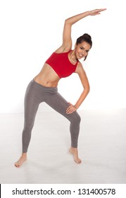Beautiful smiling young woman with a fit shapely body standing doing yoga exercises bending to the side with her arm raised