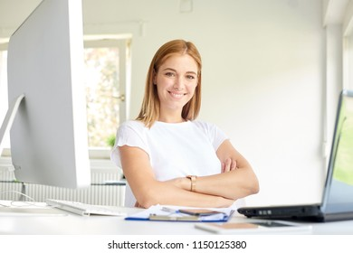 Beautiful smiling young woman with folded arms sitting at office desk while looking at camera and smiling. Home office.