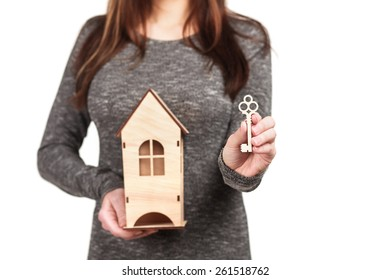 Beautiful smiling young woman in grey dress with long hair, holding small wooden house and key for it in her hands,  isolated on white background, investment and payment concept