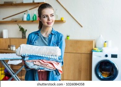 beautiful smiling young woman holding laundry and looking away