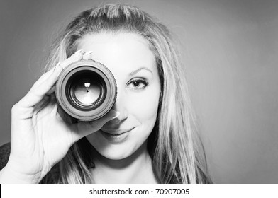Beautiful smiling young woman holding camera lens like it was spyglass. Black & White