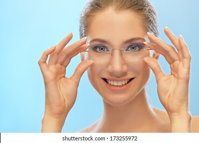 Beautiful smiling young woman holds her hands glasses, on blue background.