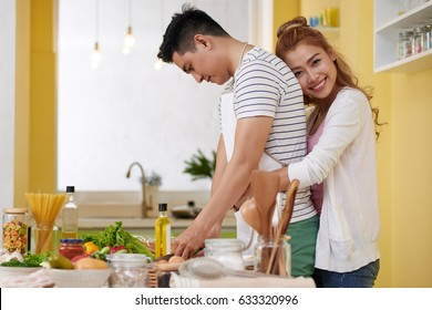 Beautiful smiling young woman hugging her cooking husband