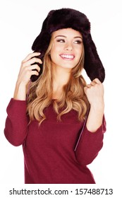 Beautiful smiling young woman with long blond hair in a winter cap holding the ear flaps in her hand isolated on white