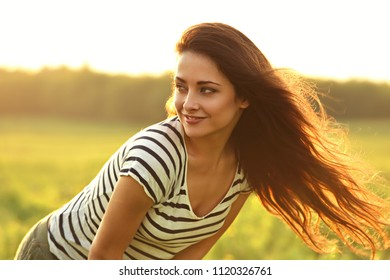 Beautiful smiling young woman looking happy with long amazing bright hair on nature bright sunset summer background. Closeup portrait