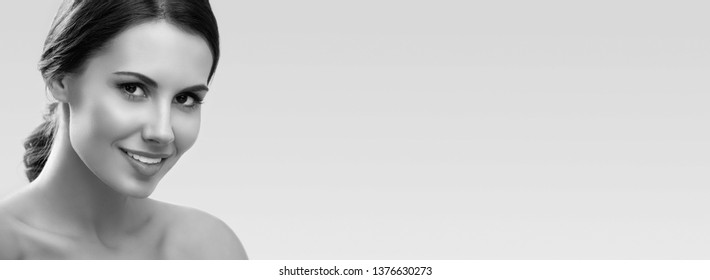 Beautiful smiling young woman with naked shoulders, on grey background, with big copy space area, for some text, advertising or slogan. Black and white.