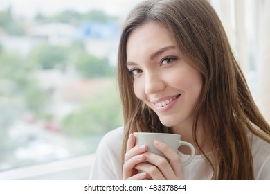 Beautiful smiling young woman with natural make up and long eyelashes holds a cup with coffee or tea.
