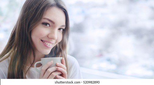 Beautiful smiling young woman with natural make up and long eyelashes holds a cup with hot coffee or tea. Winter season.
