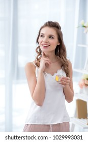 beautiful smiling young woman in pajama holding bottle of perfume and looking away