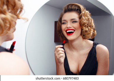 Beautiful smiling young woman with perfect make up, red lips, retro hairstyle in black dress, looking in mirror. Horizontal view.