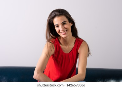 A beautiful smiling young woman in a red dress sitting on a sofa.