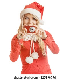 Beautiful smiling young woman in Santa Claus hat and red shirt with camera, isolated on white background.