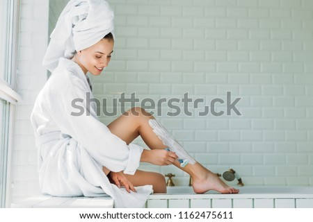 beautiful smiling young woman shaving leg with razor in bathroom
