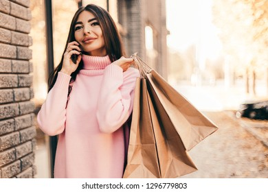 Beautiful smiling young woman with shopping  bags and phone on the street.