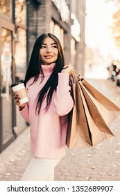 Beautiful smiling young woman with shopping  bags and coffee on the street.