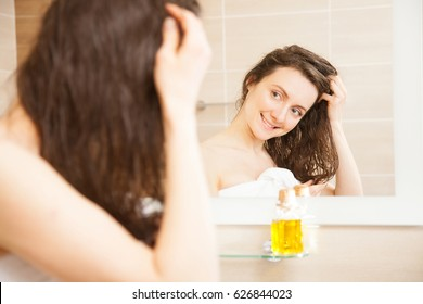 Beautiful smiling young woman spreading oil mask over her hair in front of a mirror; concept of haircare