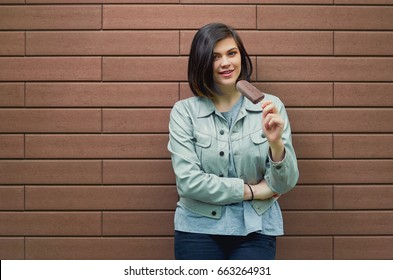 Beautiful smiling young woman in a stylish leather jacket tastes ice cream in chocolate glaze near a textured brown brick wall.