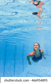 Beautiful smiling young woman swimming underwater