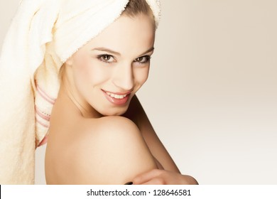 beautiful smiling young woman with a towel on her head after bath