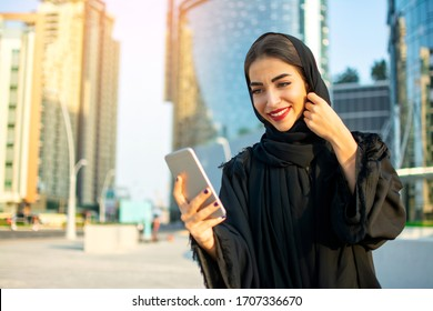 Beautiful smiling young woman using smartphone on the street.