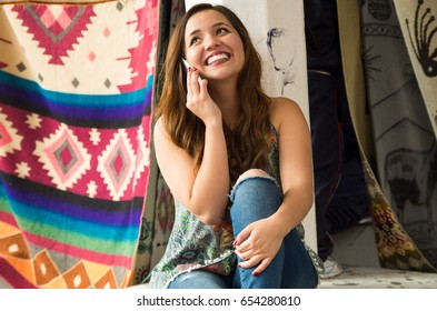 Beautiful smiling young woman using her celphone, andean traditional clothing textile yarn and woven by hand in wool, colorful fabrics background