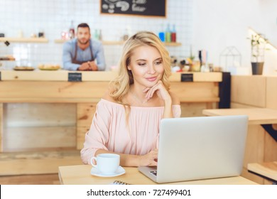 beautiful smiling young woman using laptop in cafe