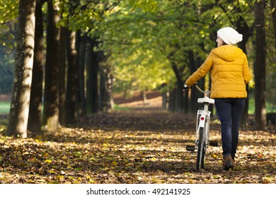 Beautiful smiling young woman walking with bicycle in Autumn park