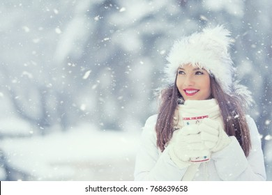 Beautiful smiling young woman in warm clothing with cup of  hot tea coffee or punch.
