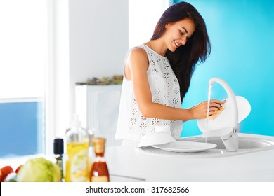 Beautiful smiling young woman washing the dishes in modern white kitchen.