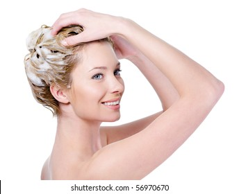 Beautiful smiling young woman washing her hair with shampoo - isolated on white