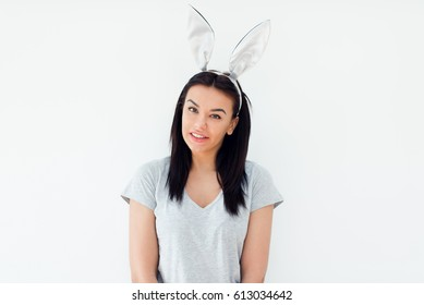 Beautiful smiling young woman wearing bunny ears and looking at the camera
