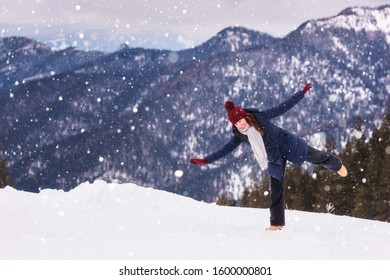 Beautiful smiling young woman in winter mountains at sunset during snowfall, outdoor travel background, happy winter concept. Jasna ski resort, Low Tatras, Slovakia (Slovensko)