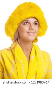 Beautiful smiling young woman in yellow fur hat, isolated on white background.