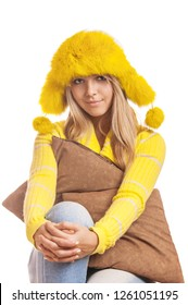 Beautiful smiling young woman in yellow fur hat with a brown pillow, isolated on white background.