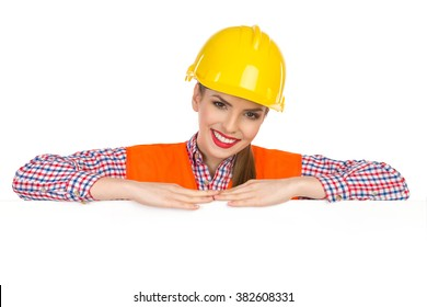 Beautiful smiling young woman in yellow hardhat, orange reflective vest and lumberjack shirt posing behind big white poster and looking at camera. Studio shot isolated on white.
