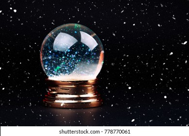 Beautiful snow ball with snowfall inside over black background with snowfall