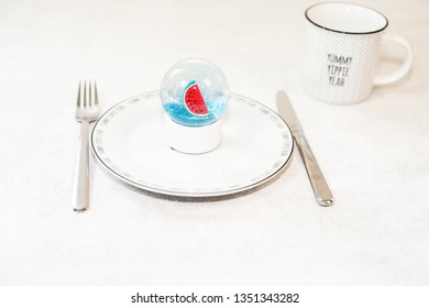 Beautiful snow ball with watermelon and glitter inside on white plate. Christmas on the beach concept.