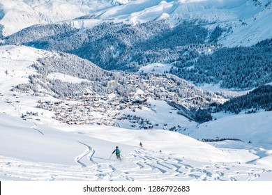 Beautiful snow capped mountains with Arosa village. Back country skier in the foreground leave their tracks in the deep snow.