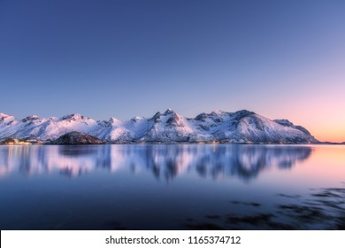 Beautiful snow covered mountains and colorful sky reflected in water at night. Winter landscape with sea, snowy rocks, blue sky, reflection, sunlight at sunset. Lofoten islands, Norway at dusk. Nature