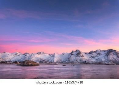 Beautiful snow covered mountains and colorful sky reflected in water at night. Winter landscape with sea, snowy rocks, sky, pink clouds, reflection at sunset. Lofoten islands, Norway at dusk. Nature