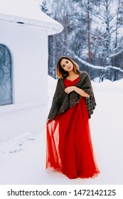 Beautiful snow maiden girl with red hair on february nature. Beautiful redhead retro woman in red gown and with long gloves on background of winter nature. Snow fall in february. Long retro gown