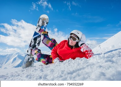 beautiful snowboard girl lies on the snow looking at the camera.