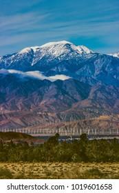 Beautiful snow-covered Mount San Jacinto rises above the Coachella Valley and San Gorgonio Pass Wind Farm, Palm Desert, California