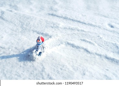 Beautiful snowman on natural snowdrift. Little funny white snowman in the snowbank.