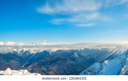 Beautiful snowy ridge of caucasus mountains under clear blue sky in Krasnaya Polyana, Sochi, Russia.