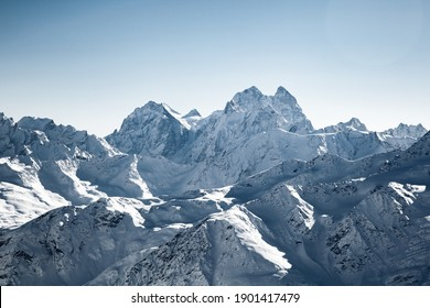 Beautiful snowy white high mountains against the blue sky. The sun is shining brightly. The mountains of Elbrus. Resorts of the Caucasus. Winter landscape. Panorama of the mountains.